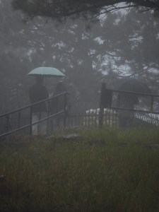 people under umbrellas in the fog and rain at a gravesite