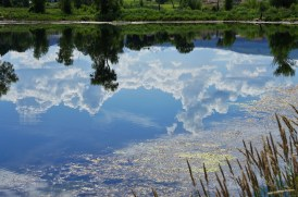 clear blue mountain pond reflecting sky, clouds and green landscape