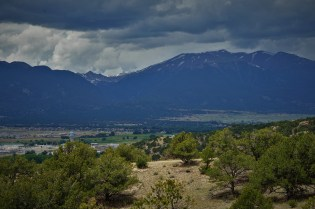 view of the Collegiate Peaks mountain range with greenery in the foreground and stormy skies
