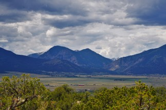view of the Collegiate Peaks mountain range with greenery in the foreground and cloudy skies