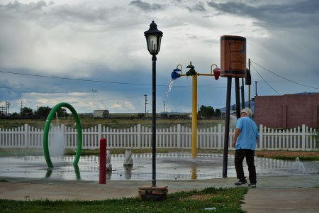 man by water park features at small city park