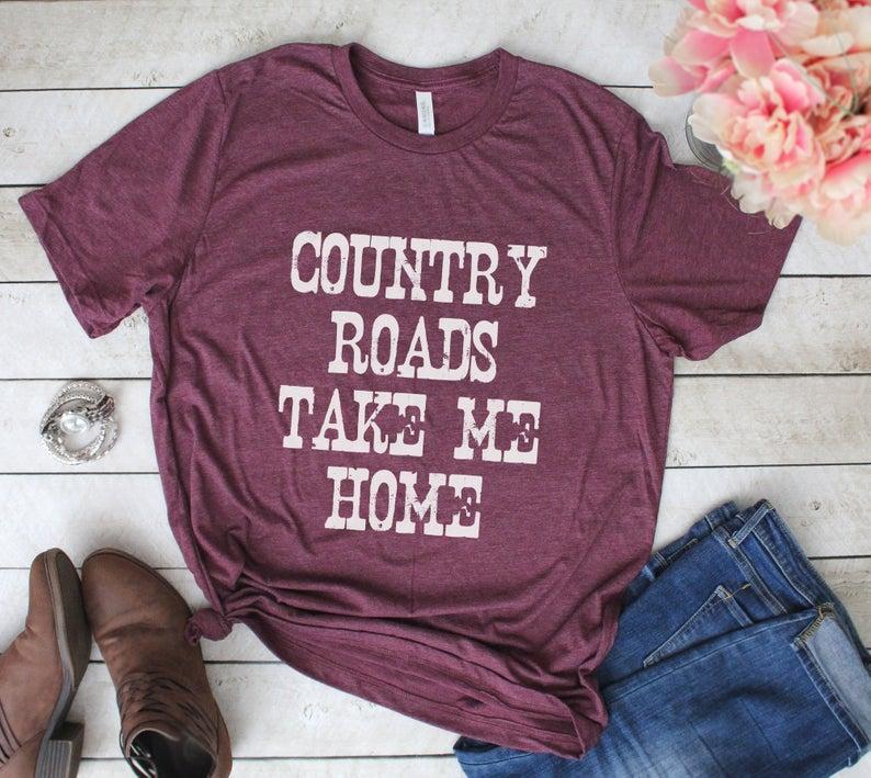 Country vaatteet johon kuuluu farkut, bootsit ja t-paita.
