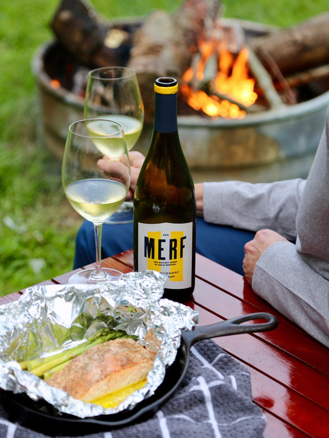 Glass of white wine enjoyed around with campfire with a salmon dinner