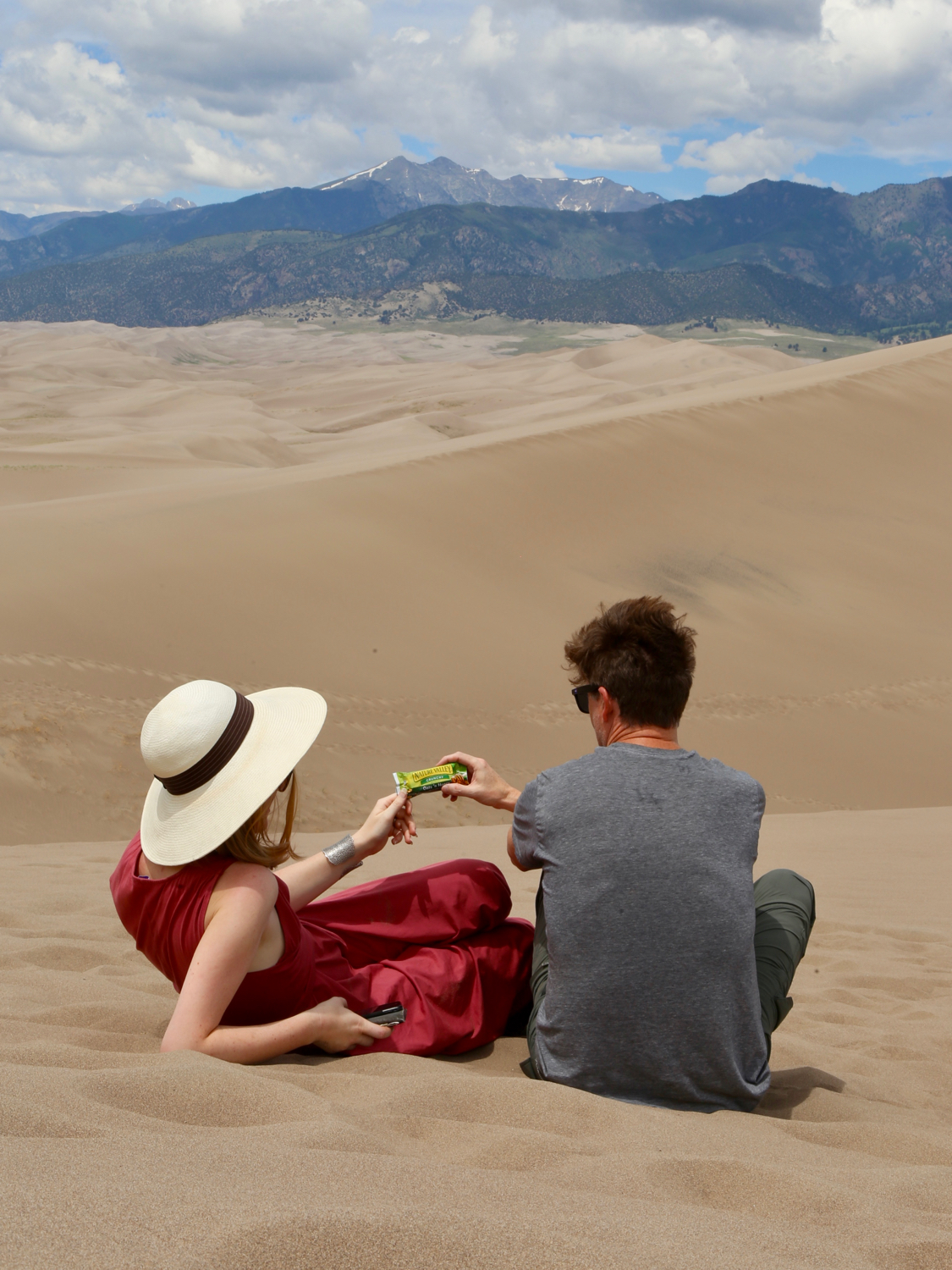 Woman and man sharing a granola bar in Great Sand Dunes National Park
