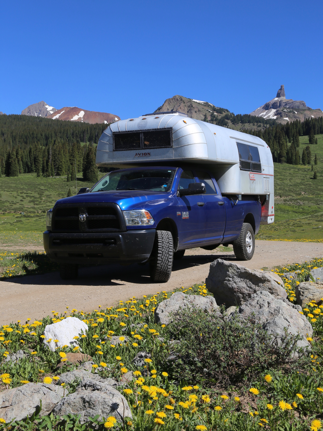Vintage truck camper on a blue truck on a dirt road in the Colorado wilderness