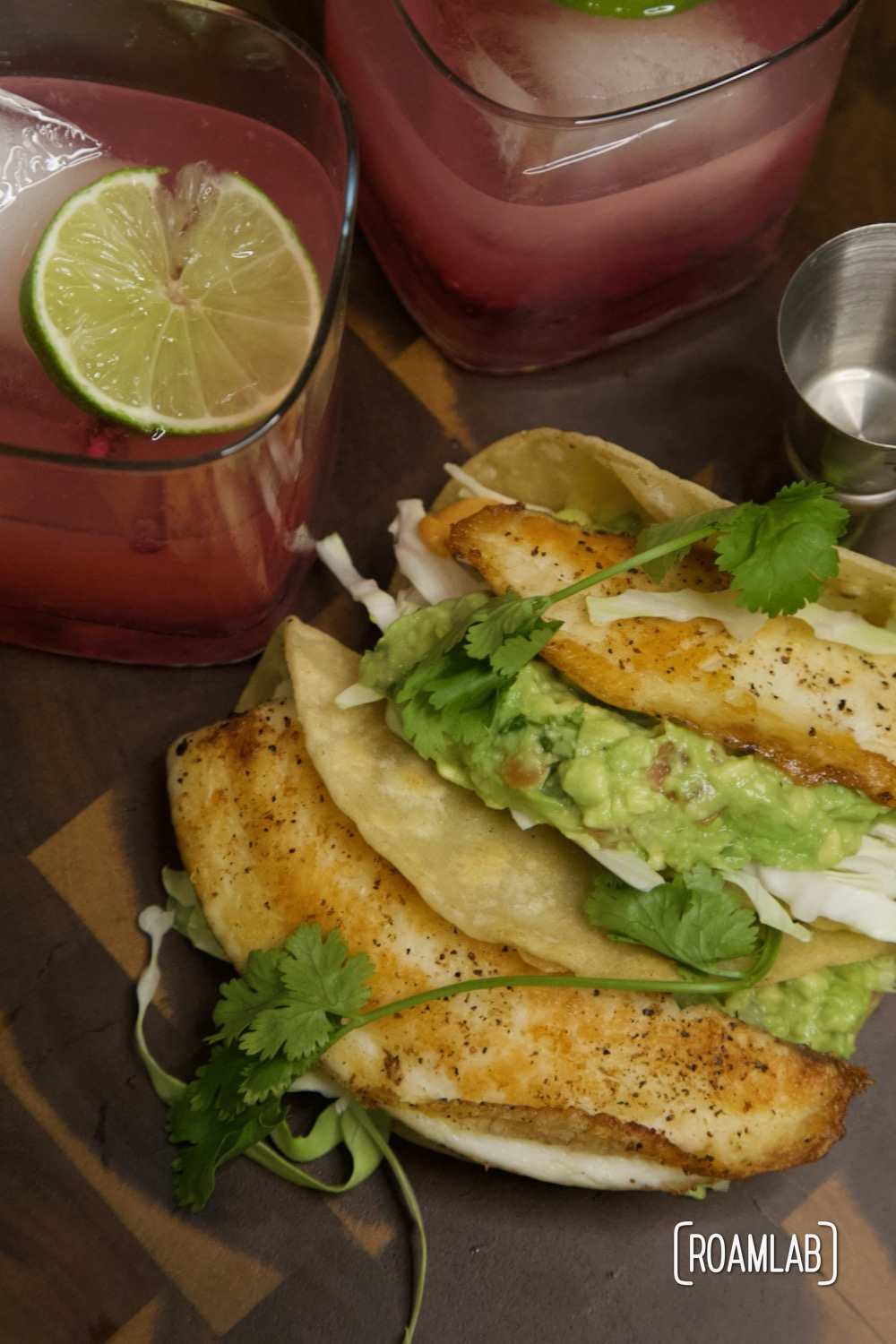 Tilapia fish tacos with guacamole and pomegranate margaritas.