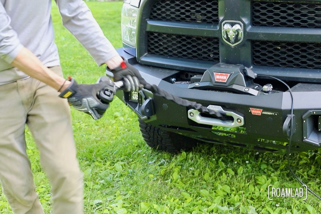 Man pulling rope out of a front bumper mounted winch.