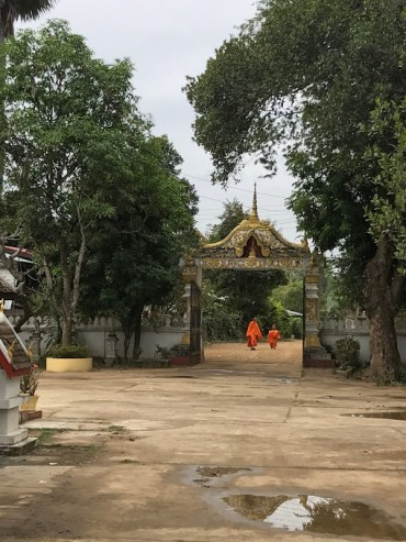 Two monks walking into Wat Tao Hai.