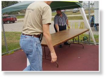 A photo of putting the table under the canopy at the Roanoke Public Library..