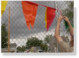 A photo of attaching flags to nearby fencing to grab even more attention.