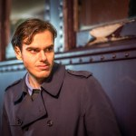 Brooding Actor in front of rail carriage