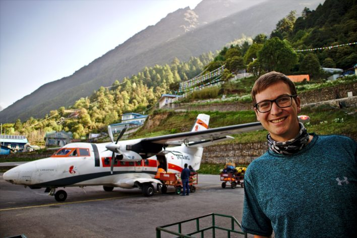 Everest Base Camp Itinerary | Rob is standing in front of the plane in the most dangerous airport in the world in Lukla