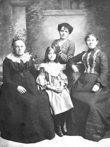 L-R: Miriam Buxton (née Hall), her great granddaughter Isabella Cicely Hobson, granddaughter Annie Elizabeth Hobson (née Ling), and daughter Mary Ann Ling (formerly Buxton, née Hall) c. 1907. Source: Courtesy of the National Fairground Archive.