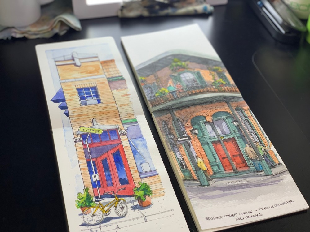 Two Sketchbooks over black desk with brushes. Brick building with red door watercolor and ink sketch