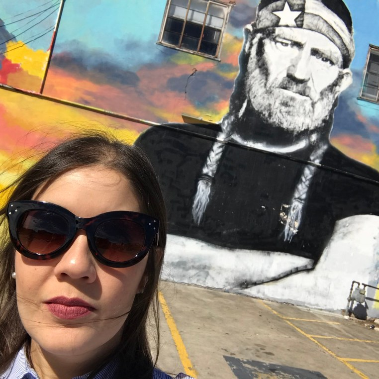 Woman with sunglasses in front of Willie Nelson Mural in Austin Texas