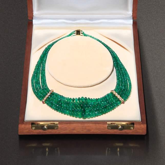 Collana firmata Faraone composta da 5 fili di boule di smeraldo con due inserti in oro giallo 18 carati, diamanti taglio brillante e rubini cabochon