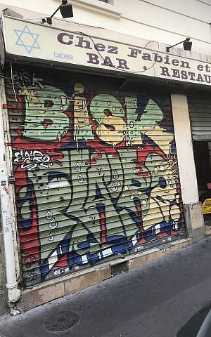 A Jewish bar-restaurant with graffiti painted on the shutters. (Robert Sarner/ Times of Israel)