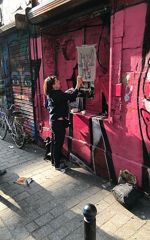 Shiry Avny spraypaints a stencil during her street art demonstration near the end of her tour. (Robert Sarner/ Times of Israel)