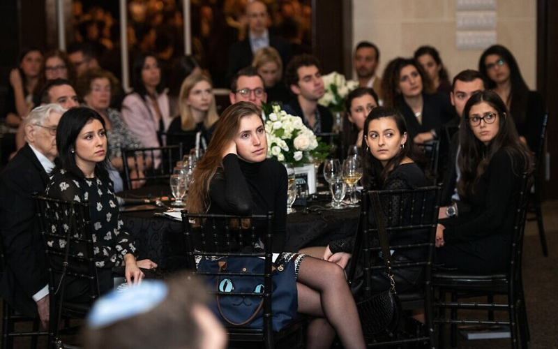 Attendees watch a presentation at the Dinner of Miracles in Toronto, December 15, 2019. (Liora Kogan)