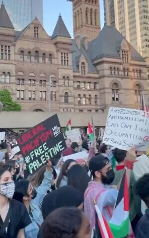 A woman holds a sign that says 'Liberal pacifism will not free Palestine' at a pro-Palestinian rally held during Israel's Operation Guardian of the Walls, in Nathan Phillips Square, downtown Toronto, May 15, 2021. (Screenshot YouTube)
