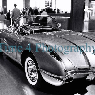 1958 Chevrolet Corvette, rear and side view, at a car show. In the background many visitors can be seen. Black and white picture