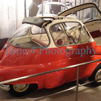 Red Romi Isetta bubble Car, with white roof top, side view at a car show