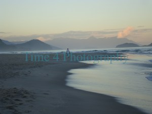 Beach at dusk showing island and mountain with clouds on the horizon