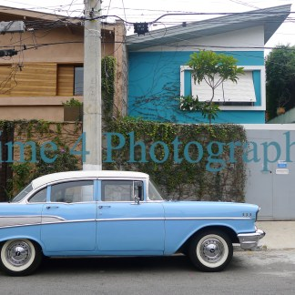 1957 Chevrotet Bel Air with blue body and white rooftop, parked at a curb in front of two houses, creating a very interesting visual effect.