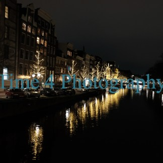 Canal in Amsterdam at night, with lights reflecting on the water. It is Christmas time and all the houses along the canal are brightly decorated.