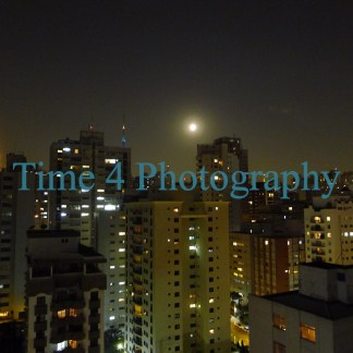 Tall buildings at night in the city of Sao Paulo, in Brazil. Several apartments have their lights on and the full moon is shining over the buildings.