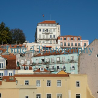 A cluster of typical portuguese houses in Lisbon, in many different light colors, which make a nice contrast against a deep blue sky.
