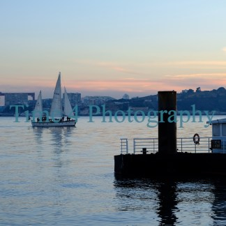 Sailboat at sunset navigating on the Tejo river in Lisbon,Portugal. On the foreground there is a small pier