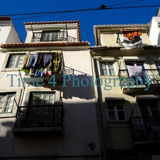 Photo depicting old apartment houses in Lisbon, with clothes in various colors hanging from iron balconies, under a deep blue sky