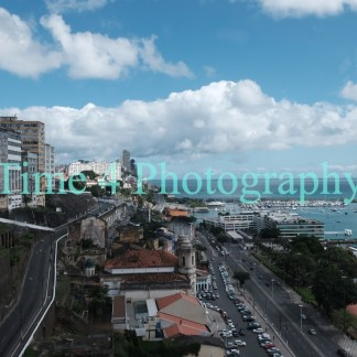 Aerial view of the city coast of Salvador in Brasil, showing tall buildings, houses, a coastal avenue and the sea on the right side