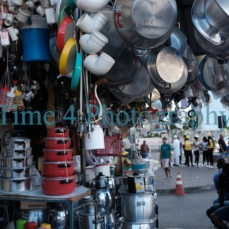 A kiosk with an array of metal pans in many sizes and other plastic household stuff at an open market in Salvador da Bahia in Brasil