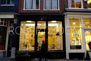 A small art gallery in Amsterdam at night, through the windows one can see the lighted interior