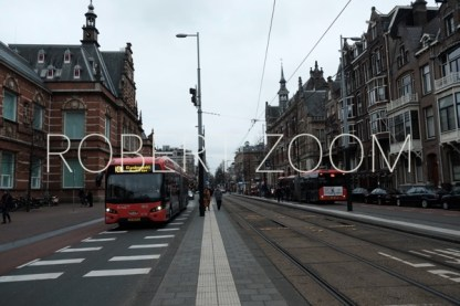 On a bus lane of a wide avenue of Amsterdam, a red bus is coming with its headlights on.It is dusk time and few people are on the street.