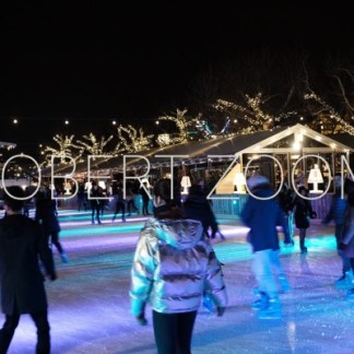 On a cold winter night in Amsterdam, several people are ice-skating.The rink is lit by multi colored light streaks and the sky is very black.