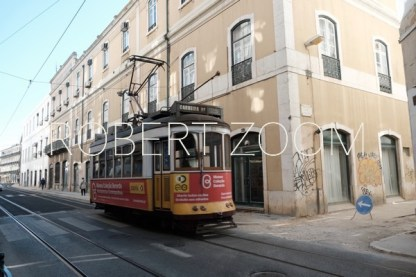 An old red streetcar is passing in front of a building at Lisbon downtown.Those streetcars are still being used in all of Portugal.