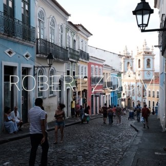 A typical street in the historic centre of Salvador da Bahia, with mall shops in multi color houses selling all kind of typical souvenirs and a church.
