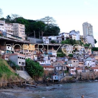 A slum by the sea in Salvador da Bahia, Brazil. Over it one can see a viaduct and far above a tall building points to a richer part of the city.
