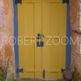 A rustic wooden yellow door in the old style, in a light blue color frame. The wall around this door is pink,but the paint has peeled of.