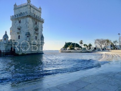 The famous Belem Tower in Lisbon,Portugal, at sunset. It is almost dusk and the sea is a mirror of the blue sky.