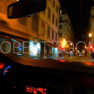 A deserted street of the restaurants district of Lisbon dowtown at night, with some streetlamps on , as seen from inside a taxi.