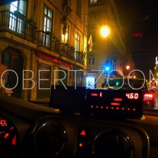 A nocturnal street view of Lisbon, seen from inside a taxi
