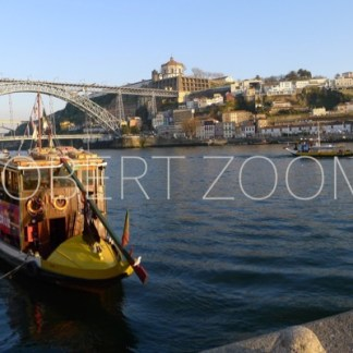 A yellow boat is anchored near one margin of the Douro river in the city of Porto, in Portugal. In the background one can see a bridge.