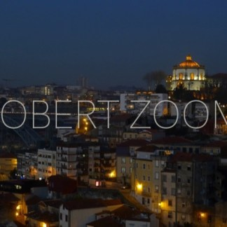 The old city of Porto, in Portugal, seenfrom above at night . The sky is dark blue and some streetlights are already on.