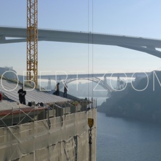 construction workers are renovating a building located on the margin of the Douro river in Porto, Portugal. The river and 2 bridges can be seen in this picture