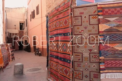 Red and orange color rugs hanging on a wall in a narrow street in Marrakech, Morocco