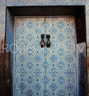 A white arabic door with blue frame and blue drawings